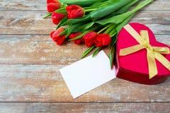 Schließen Sie oben von den roten Tulpen, vom Buchstaben und von der Pralinenschachtel Lizenzfreie Stockfotos