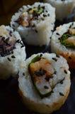 Schließen Sie oben von den Sushi, die mit schwarzen Samen des indischen Sesams besprüht werden Stockbild