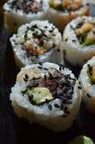 Schließen Sie oben von den Sushi, die mit schwarzen Samen des indischen Sesams besprüht werden Lizenzfreie Stockfotos