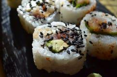 Schließen Sie oben von den Sushi, die mit schwarzen Samen des indischen Sesams besprüht werden Stockfoto