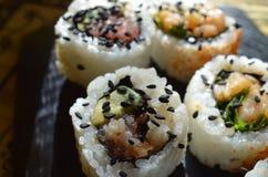 Schließen Sie oben von den Sushi, die mit schwarzen Samen des indischen Sesams besprüht werden Stockbilder