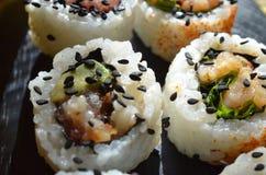 Schließen Sie oben von den Sushi, die mit schwarzen Samen des indischen Sesams besprüht werden Lizenzfreies Stockfoto