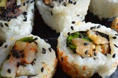 Schließen Sie oben von den Sushi, die mit schwarzen Samen des indischen Sesams besprüht werden Lizenzfreie Stockbilder