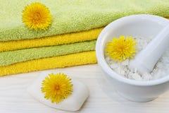 Schließen Sie oben von den Tüchern, von der Seife und vom Seesalz auf dem weißen hölzernen Hintergrund mit Löwenzahnblumen Stockfoto