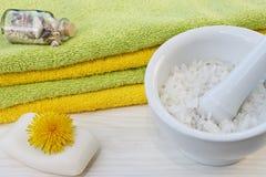 Schließen Sie oben von den Tüchern, von der Seife und vom Seesalz auf dem weißen hölzernen Hintergrund mit Löwenzahnblumen Lizenzfreie Stockfotos