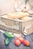 Schließen Sie oben von den Tomaten und von den Gurken über Holztisch vor einem offenen Picknickkorb Abbildung der roten Lilie Stockbilder