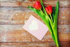 Schließen Sie oben von den Tulpen und von der Grußkarte mit Herzen Stockfoto