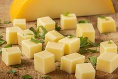 Schließen Sie oben von den Würfeln des gelben Käses mit Kräutern Lizenzfreie Stockfotografie