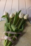 Schließen Sie oben von den weißen Tulpen und vom leeren Papier oder beschriften Sie Stockfotos