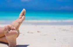 Schließen Sie oben von den weiblichen Füßen auf weißem sandigem Strand Stockfoto