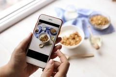 Schließen Sie oben von den weiblichen Händen, die den Handy halten, der ein Foto von Granolagetreide, von Milchjoghurt und von nä Stockfoto