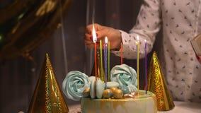 Schließen Sie oben von den weiblichen Händen, die Kerzen auf geschmackvollem Geburtstagskuchen beleuchten Prepearing für Partei stock footage