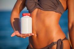 Schließen Sie oben von den weiblichen Händen mit Flasche Stockfoto