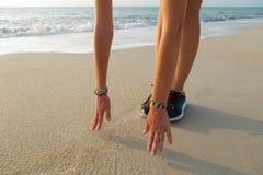 Schließen Sie oben von den weiblichen Händen und von den Füßen auf dem Strand lizenzfreie stockfotos