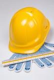Schließen Sie oben von den Werkzeugen des Erbauers - Sturzhelm, Arbeitshandschuhe und Machthaber vorbei Stockfoto