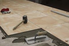 Schließen Sie oben von den Werkzeugen eines Arbeiters auf einem Boden, der mit Ziegeln gedeckt wird Stockfoto
