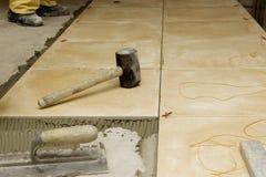 Schließen Sie oben von den Werkzeugen eines Arbeiters auf einem Boden, der mit Ziegeln gedeckt wird Lizenzfreie Stockfotos