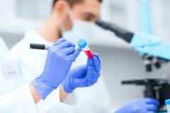 Schließen Sie oben von den Wissenschaftlerhänden mit Reagenzglas im Labor stockfotos