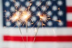 Schließen Sie oben von den Wunderkerzen, die über amerikanischer Flagge brennen Lizenzfreie Stockbilder
