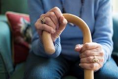 Schließen Sie oben von der älteren Frau, die im Stuhl sitzt, der gehenden Stock hält Stockfotos
