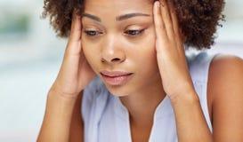 Schließen Sie oben von der afrikanischen jungen Frau, die ihren Kopf berührt Lizenzfreies Stockfoto