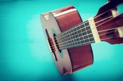 Schließen Sie oben von der Akustikgitarre gegen einen hölzernen Hintergrund lizenzfreie stockbilder