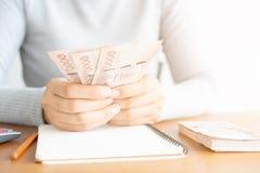 Schließen Sie oben von der asiatischen Frau mit dem Taschenrechner, der Geld zählt Frau berechnen die Ausgabe zu Hause lizenzfreie stockfotografie
