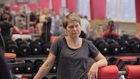 Schließen Sie oben von der athletischen Frau, die schwitzt, eine Pause nach machend, ausarbeiten Das Mädchen spricht in der Turnh stock footage