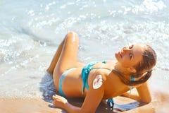 Schließen Sie oben von der attraktiven jungen Frau auf dem Strand, der Sonnencreme aufträgt Lizenzfreie Stockfotografie