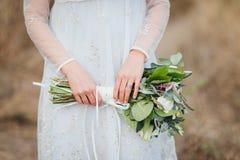 Schließen Sie oben von der Braut, die den Hochzeitsblumenstrauß hält lizenzfreies stockfoto