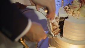 Schließen Sie oben von der Braut und von Bräutigam, die ihre Hochzeitstorte schneiden stock video
