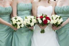 Schließen Sie oben von der Braut und von Brautjungfern, die Blumen halten lizenzfreie stockfotografie