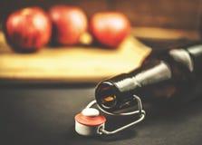 Schließen Sie oben von der Flasche und von den roten Äpfeln auf hölzernem Hintergrund Stockbild
