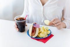 Schließen Sie oben von der Frau, die Chips, Hotdog und Kolabaum isst Stockfoto