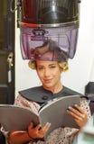 Schließen Sie oben von der Frau, die ein Buch in ihren Händen hält und unter eine alte Haartrocknerstuhlhaube, in einem unscharfe Lizenzfreie Stockfotos