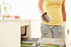 Schließen Sie oben von der Frau, die Küchen-Abfall im Behälter aufbereitet Stockbild