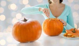 Schließen Sie oben von der Frau, die Kürbise für Halloween schnitzt Stockfotos