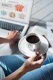Schließen Sie oben von der Frau, die Kaffeetasse hält und Laptop verwendet Stockfotos