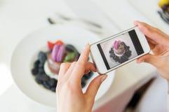 Schließen Sie oben von der Frau, die Lebensmittel durch Smartphone darstellt Stockbild