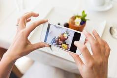 Schließen Sie oben von der Frau, die Lebensmittel durch Smartphone darstellt Stockfoto