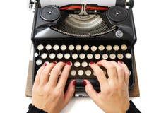 Schließen Sie oben von der Frau, die mit alter Schreibmaschine schreibt Stockfotografie