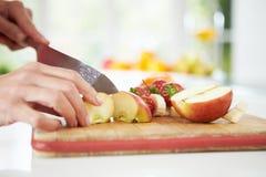 Schließen Sie oben von der Frau, die Obstsalat zubereitet Stockfotos