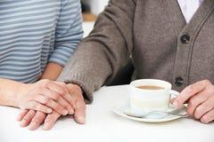 Schließen Sie oben von der Frau, die Tasse Tee mit älterem Elternteil teilt Lizenzfreies Stockbild