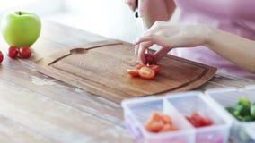 Schließen Sie oben von der Frau, die zu Hause Gemüse hackt stock footage