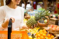 Schließen Sie oben von der Frau mit Ananas im Lebensmittelgeschäftmarkt Lizenzfreie Stockbilder
