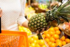 Schließen Sie oben von der Frau mit Ananas im Lebensmittelgeschäftmarkt Stockfoto