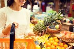 Schließen Sie oben von der Frau mit Ananas im Lebensmittelgeschäftmarkt Lizenzfreie Stockfotografie