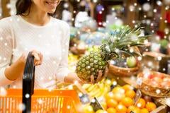 Schließen Sie oben von der Frau mit Ananas im Lebensmittelgeschäftmarkt Stockfotos
