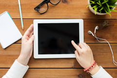 Schließen Sie oben von der Frau mit Tabletten-PC auf Holztisch Lizenzfreie Stockfotografie
