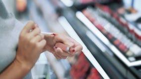 Schließen Sie oben von der Frau, welche die Hand, die Lippenstift in den Kosmetik wählt, kaufen, Zeitlupe stock video